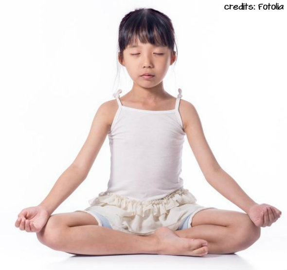 Little girl practicing yoga isolated on white background