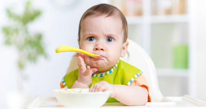 funny baby girl eating food on kitchen